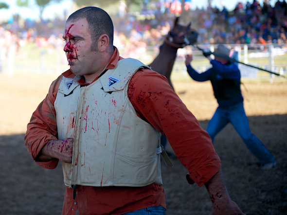 Paul Bianchi of Hollister, CA walks out of the arena after getting kicked in the head by a bronc at the Marysville Stampede in Marysville, CA.